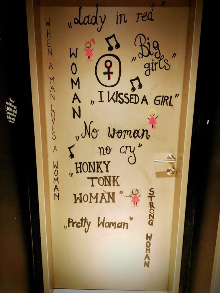 Women's bathroom door with gender appropriate song lyrics