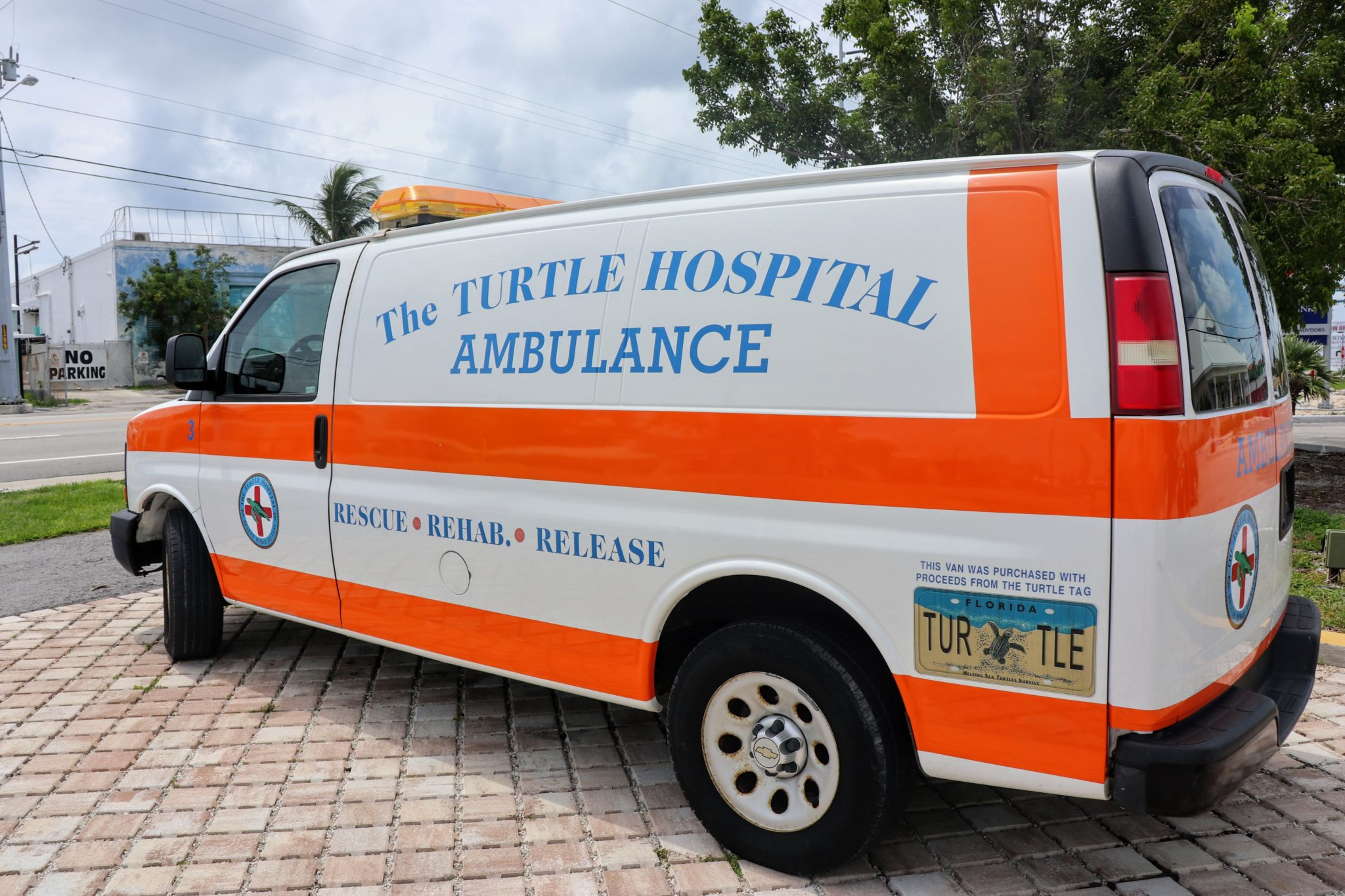 A bright orange and white Turtle Hospital Ambulance with a Florida state sea turtle license plate.