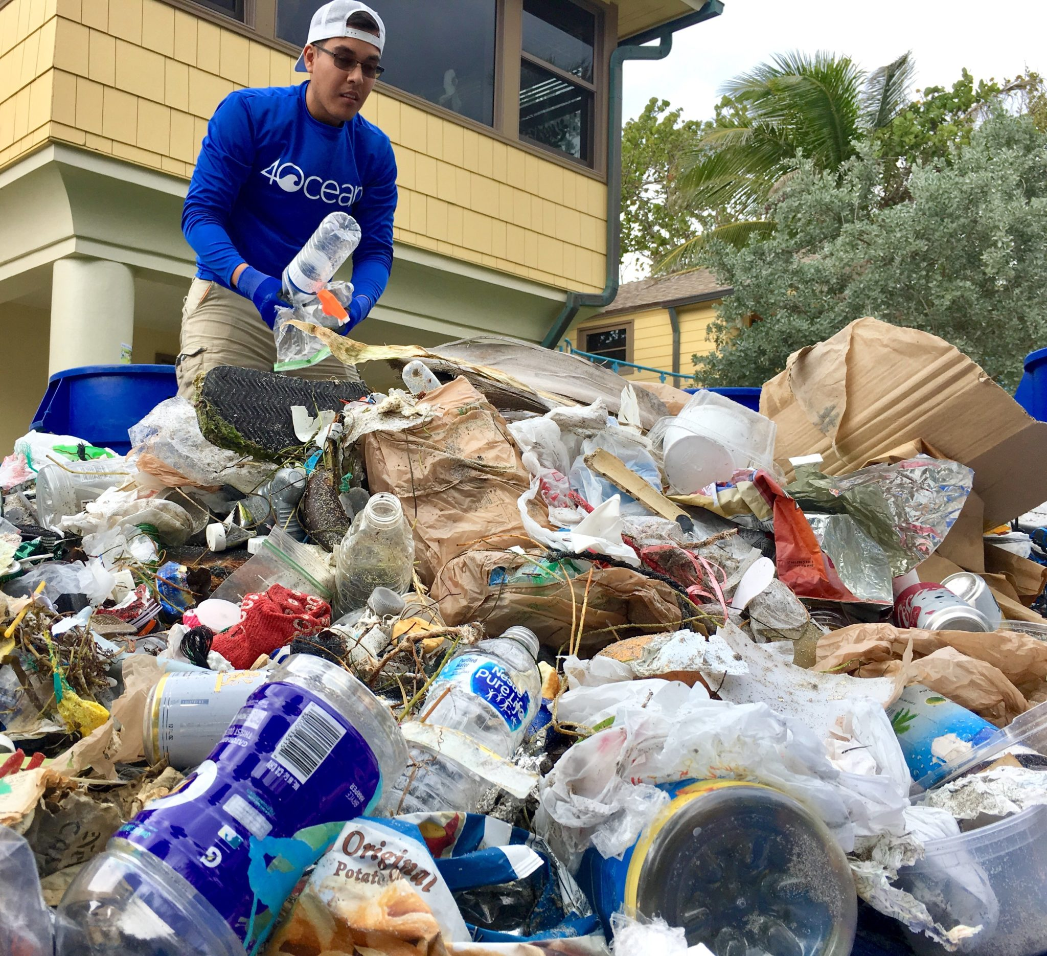 Volunteer standing next to pile of trash he helped pick up off of the beach.