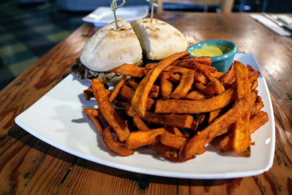 Pepper 'Steak' and Swiss vegan or vegetarian sandwich with close up of truffle fries